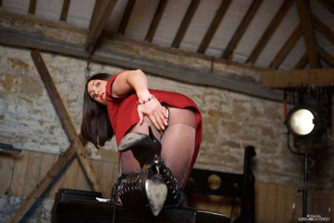 Miss Hybrid playing with sex toys in the dungeon.